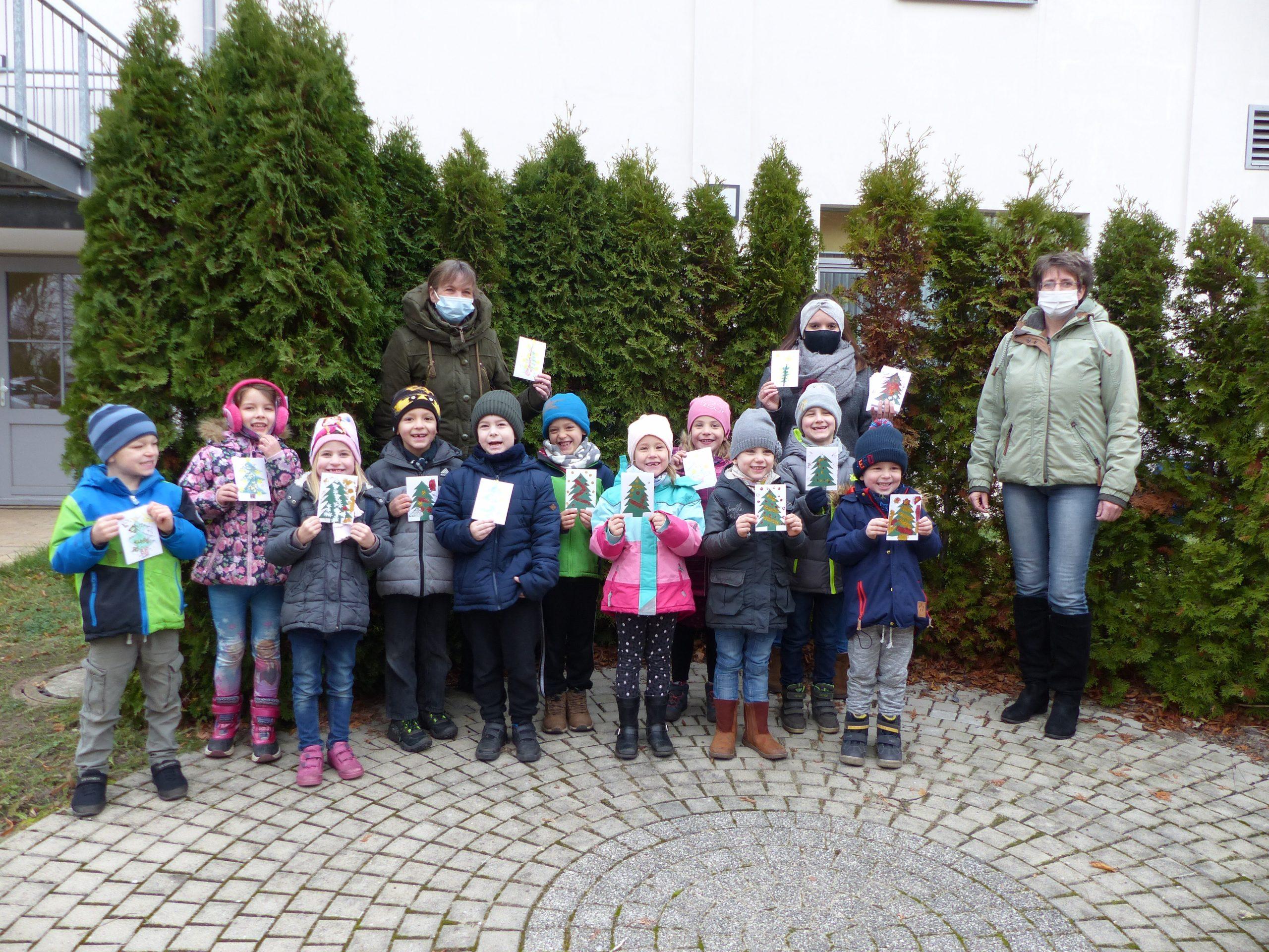 Kinder in Brandenburg a. d. Havel halten selbstgemalte Postkarten hoch